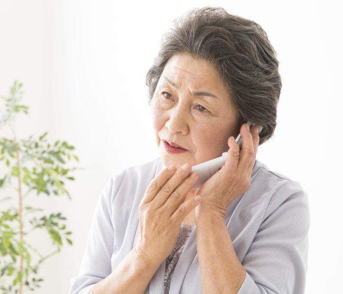 電話で重要な話をするシニア女性