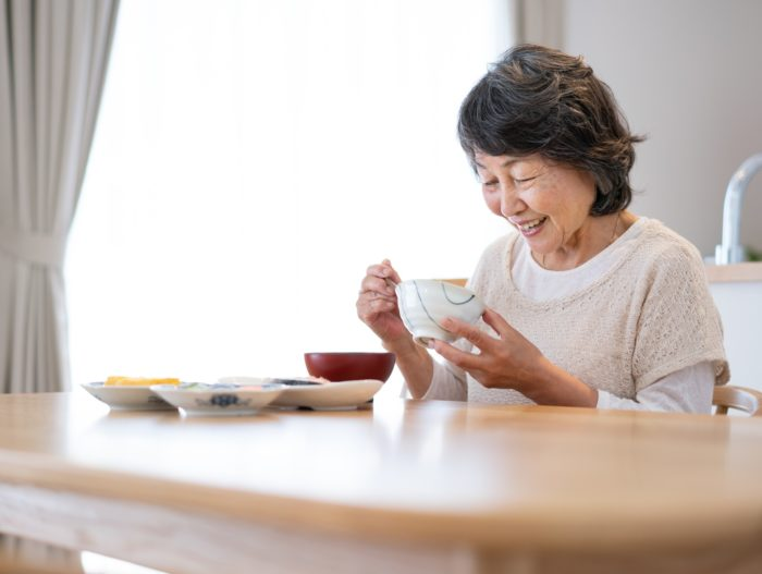 一人で食事をする高齢女性