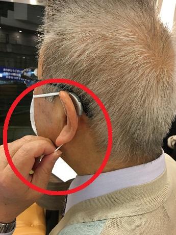 補聴器を装用しながら、マスクの下側の紐を引っ張る様子