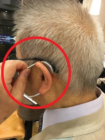 補聴器を装用しながら、マスクの上側の紐を引っ張る様子
