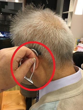 補聴器を装用しながら、マスクの上側の紐からマスクを外す様子