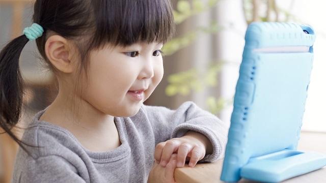 子どもがスマホ(タブレット)で動画を見ている画像